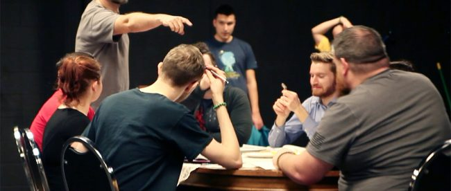 Archer (above, pointing) directing the student actors as they run through a scene around the table.
